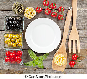 Empty plate on wooden table with fruits and utensils