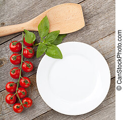 Empty plate on wooden with tomatoes and utensil