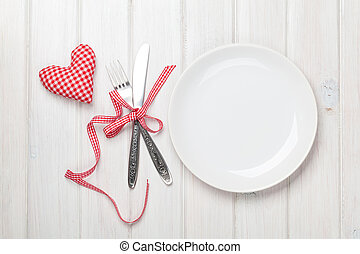 Empty plate, silverware and valentines day heart shaped toy