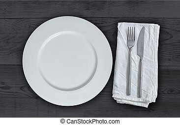 Empty plate with cutlery on anthracite wood