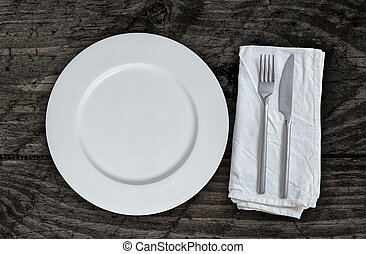 Empty plate with cutlery on brown vintage wood