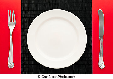 empty plate with fork and knife - empty white plate on black...
