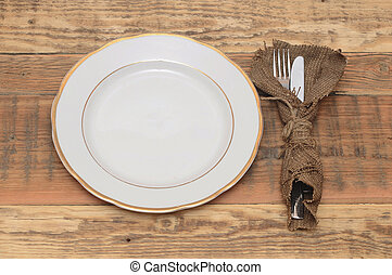 Empty plate with fork and knife on wooden table.