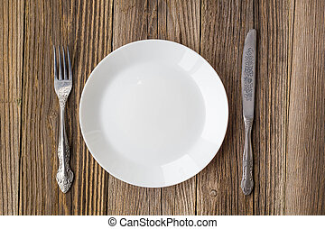 empty plate with knife and fork on empty wooden table