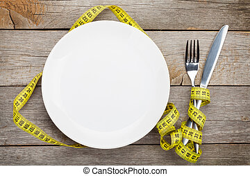 Empty plate with measure tape, knife and fork