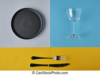 Empty plates, forks and glass of wine on colors background, mockup.