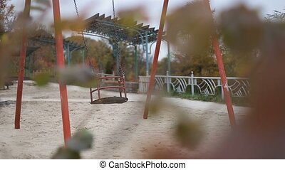 Empty playground swing swaying in autumn time - Empty...