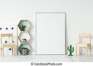 Empty poster, geometric shelves and small wooden chairs standing on the floor in white baby room interior. Paste your picture here