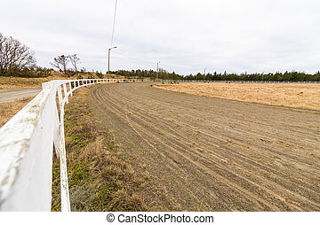 Empty race track for racing horses, sand track and white fence