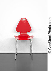 empty red chair at a white wall