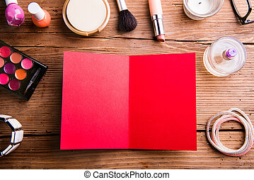 Empty red greeting card laid on table. Make-up products.