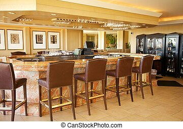 An empty bar, made of marble, with stools at a resort