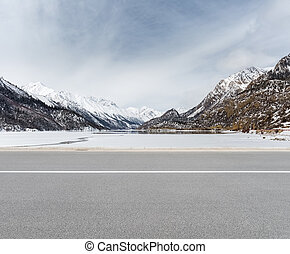 empty road in tibetan plateau - empty road with snow...