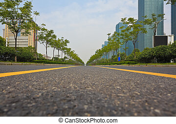 Empty road surface with modern city buildings background -...