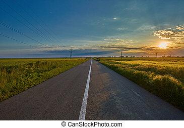 Empty road through wheat fields
