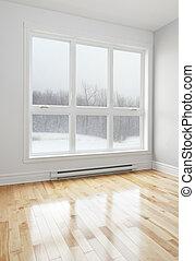Winter landscape seen through the big window of an empty room.