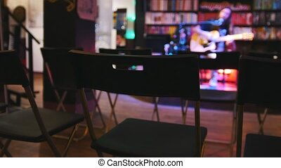 Empty room in front of the guitarist at concert - acoustic guitar, microphone, club