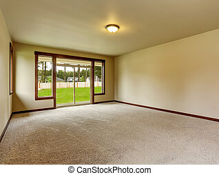 Empty room interior in beige tones and carpet floor. Also exit to backyard area. Northwest, USA