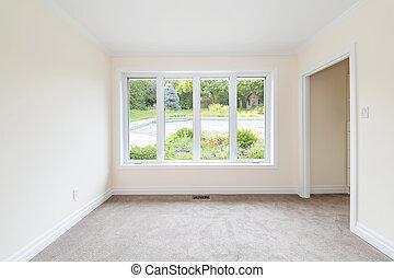 Empty room overlooking backyard - Empty room with large...