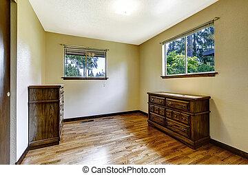 Empty room with hardwood floor and wooden furniture