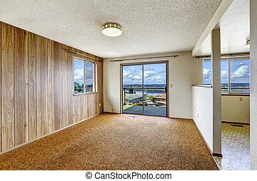 Empty room with wood plank paneled wall and carpet floor