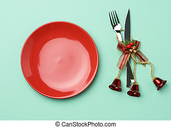 empty round red ceramic plate, knife and fork on green background