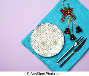 empty round white ceramic plate, knife and fork on a purple background