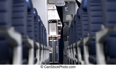 Empty row of dark blue seats inside an airplane with the cabin as background. Peaceful and tranquil interiors of commercial plane. Means of transport