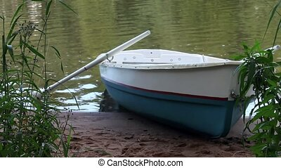 Empty rowboat on the banks - rowing boat on the beach close...