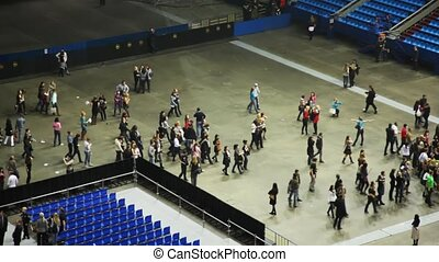 Empty rows of seats and leaving spectators in concert hall