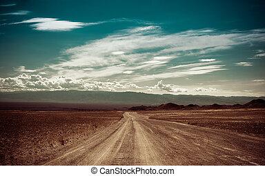 Empty rural road going through prairie under cloudy sky