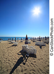 Empty sandy beach with folded and open umbrellas and sunbeds, burning sun and cloudless sky
