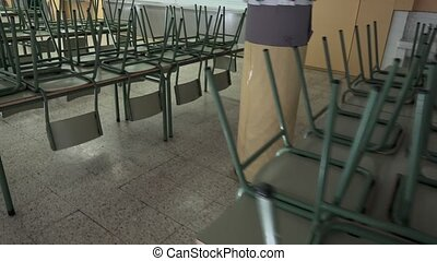 Empty school dining room with chairs turned upside down