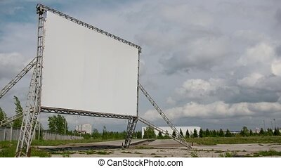Empty screen of open car cinema - time-lapse of billboard in front of clouds at sunny day