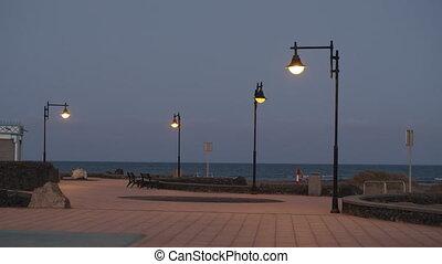 Empty seaside promenade with streetlights on for nobody