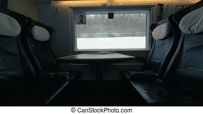 Empty seats in moving express train - Four empty seats and a...