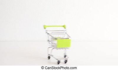 Empty shopping cart rolling and stopping video. Shop small trolley riding on a table on white background