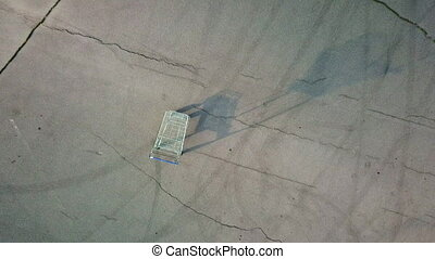 Single empty shopping cart standing on chappy asphalt square, zoom in video, top view