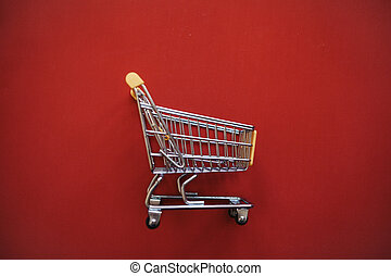 Empty shopping trolley on a red background