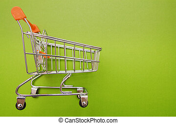 empty shopping trolley on green background with some copy space