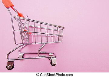 empty shopping trolley on pink background with some copy space