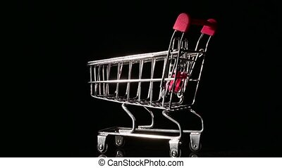 Empty shopping trolley with pink handle spinning on black background