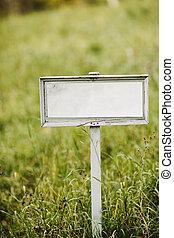 Empty signboard on a green field