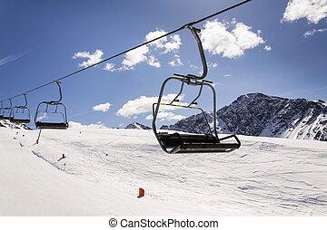 Empty ski chair lift on sunny day in Alps, Austria