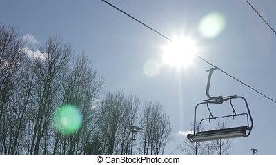 Empty ski chairlift against the sun. Winter in Belarus.
