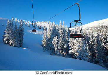 Empty ski chairlift in winter mountains above resort slopes