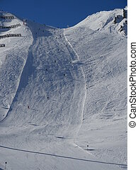 empty ski slope - Snowy slope in the mountains with blue sky