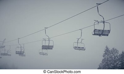 Empty skilift or chairlift in action - Mountain ski slope...