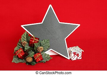 empty slate in the form of a star to write a message on a red background with red and white gifts placed on a wreath of fir for decoration of fetes