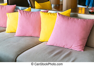 empty sofa and chair with pillows